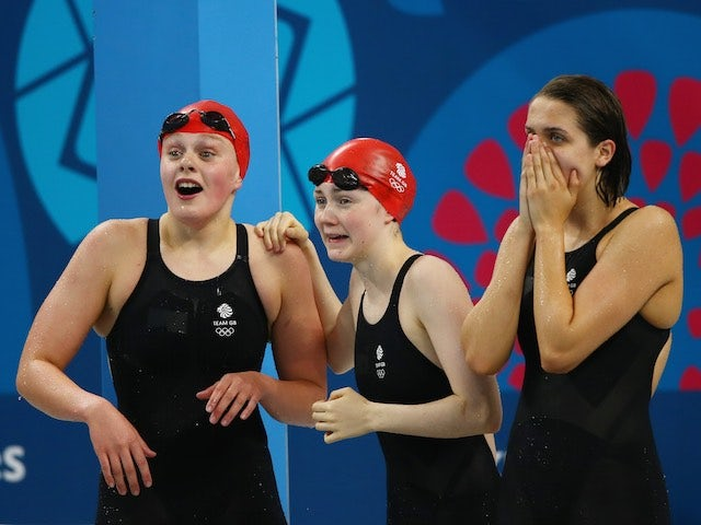 Team GB swimmers Holly Hibbott, Hannah Featherstone and Darcy Deakin react during the women's 4x200m freestyle relay at the European Games on June 27, 2015