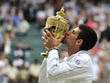 Serbian player Novak Djokovic kisses the trophy after beating Spanish player Rafael Nadal in the men's single final at the Wimbledon Tennis Championships at the All England Tennis Club, in southwest London on July 3, 2011