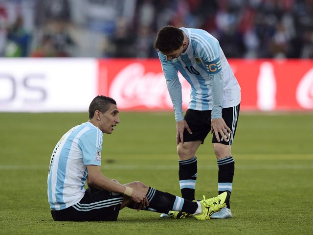 Argentina's forward Angel Di Maria (L) remains on the ground after getting injured next to Argentina's forward Lionel Messi during their 2015 Copa America final football match, in Santiago, Chile, on July 4, 2015