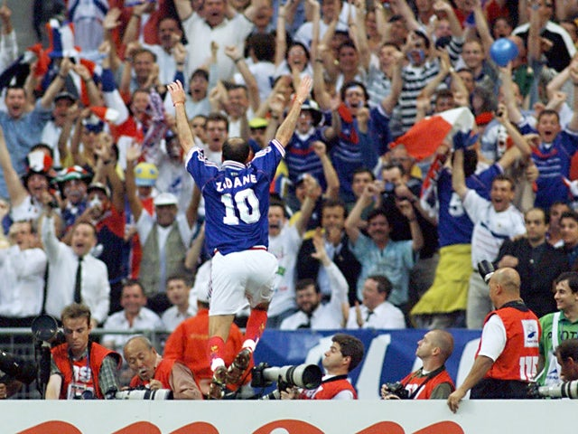 French Zinedine Zidane jumps over the barrier as he celebrates after scoring the first goal for his team 12 July outside the Stade de France in Saint-Denis, during the 1998 World Cup final match between Brazil and France
