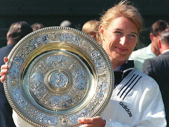 German top seed Steffi Graf holds her trophy after she won her seventh title after beating Arantxa Sanchez Vicario of Spain in the women 's singles final at the Wimbledon Tennis Championships 06 July 1996