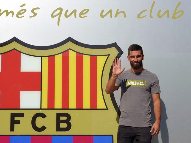 Barcelona's new player Turkish Arda Turan waves as he poses outside the Camp Nou stadium in Barcelona, prior to signing his new contract with the Catalan club, on July 9, 2015