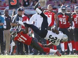 Travaris Cadet #39 of the New Orleans Saints gets tripped up along the sideline by C.J. Wilson #41 of the Tampa Bay Buccaneers in the second half of the game at Raymond James Stadium on December 28, 2014