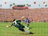 Brazilian goalkeeper Claudio Taffarel dives the wrong way as Italian midfielder Roberto Baggio's penalty kick goes over the crossbar during the shoot-out of the World Cup soccer final 17 July 1994