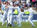 England's James Anderson (L) celebrates with teammates after taking the final wicket of Brad Haddin for 71 during play on the fifth day of the first Ashes cricket test match between England and Australia at Trent Bridge in Nottingham, central England on J
