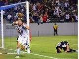 Alan Gordon of the LA Galaxy celebrates after scoring the game-winning goal before the dejected Club America defender Paolo Goltz (R) on July 11, 2015