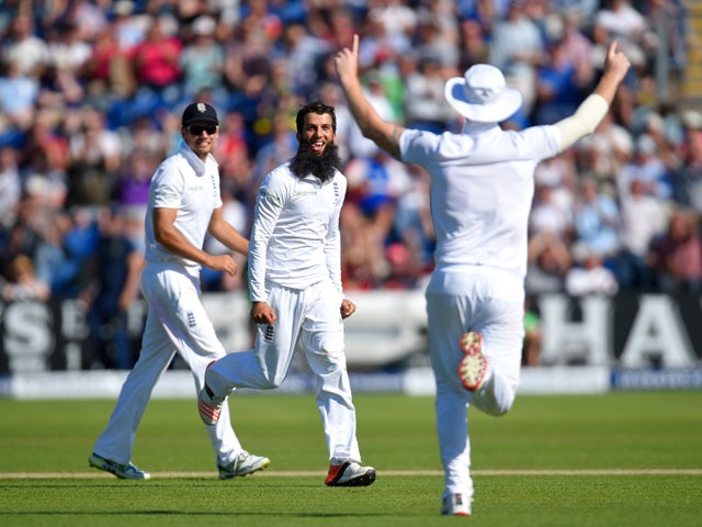 England bowler Moeen Ali celebrates with Alastair Cook and Ben Stokes after dismissing Michael Clarke during day two of the 1st Investec Ashes Test match between England and Australia at SWALEC Stadium on July 9, 2015