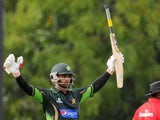 Pakistan cricketer Mohammad Hafeez raises his bat in celebration after scoring a century (100 runs) during the first One Day International (ODI) match between Sri Lanka and Pakistan at the Rangiri Dambulla International Cricket stadium in Dambulla, some 1