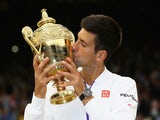 Novak Djokovic of Serbia celebrates with the trophy after winning the Final Of The Gentlemen's Singles against Roger Federer of Switzerland on day thirteen of the Wimbledon Lawn Tennis Championships at the All England Lawn Tennis and Croquet Club on July