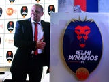 Formar Brazilian football player and team manager of Delhi Dynamos Roberto Carlos poses alongside the team shield during a press confrence in the Indian capital New Delhi on July 9, 2015