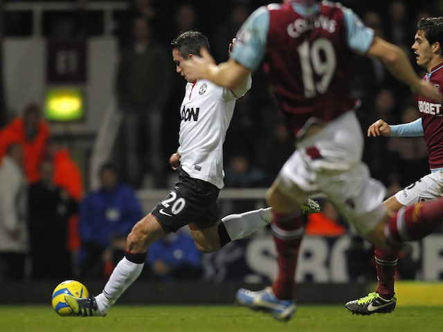 Manchester United's Dutch striker Robin Van Persie (L) shoots to score his late equalizing goal during the English FA Cup third round football match between West Ham United and Manchester United at the Boleyn Ground, Upton Park, in East London on January