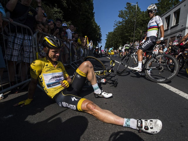 Germany's Tony Martin, wearing the overall leader's yellow jersey, sits on the ground after a fall as Poland's Michal Kwiatkowski looks at him (R), during the 191.5 km sixth stage of the 102nd edition of the Tour de France cycling race on July 9, 2015