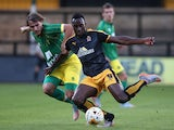 Jordon Slew of Cambridge United is tackled by Ignasi Miquel during the pre season friendly match between Cambridge United and Norwich City at the Abbey Stadium on July 17, 2015
