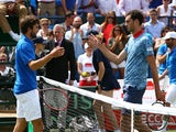 James Ward of Great Britain shakes hands at the net after his straight sets defeat against Gilles Simon of France during Day One of the World Group Quarter Final Davis Cup match between Great Britain and France at Queens Club on July 17, 2015