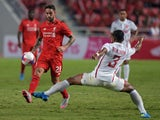 Liverpool football player Danny Ings (L) battles for the ball with Prathum Chuthong (R) of Thailand All Stars at Rajamangala stadium in Bangkok on July 14, 2015