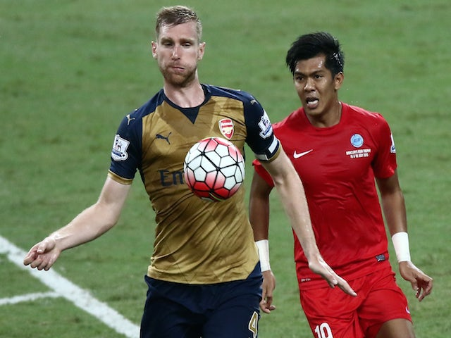 Per Mertesacker of Arsenal is checked by Khairul Amri of Singapore during the Barclays Asia Trophy match between Arsenal and Singapore at National Stadium on July 15, 2015