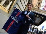 Soccer player Benjamin Stambouli holds up his new jersey from team Paris Saint-Germain July 23, 2015