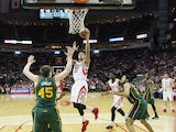 K.J. McDaniels #32 of the Houston Rockets takes the ball to the basket against Jack Cooley #45 and Grant Jerrett #17 of the Utah Jazz during their game at the Toyota Center on April 15, 2015