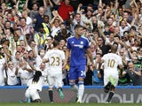 The Swansea City fans celebrate after Swansea City's French striker Bafetimbi Gomis (C floor) celebrates scoring a second equalising goal from the penalty spot for 2-2 during the English Premier League football match between Chelsea and Swansea City at St