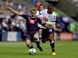 Neil Danns of Bolton Wanderers and Stephen Warnock of Derby County battle for the ball during the Sky Bet Championship match between Bolton Wanderers and Derby County at the Macron Stadium on August 8, 2015