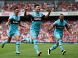 Mauro Zarate of West Ham United (C) celebrates with team mates as he scores their second goal during the Barclays Premier League match between Arsenal and West Ham United at the Emirates Stadium on August 9, 2015