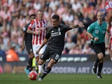 Liverpool's Brazilian midfielder Philippe Coutinho shoots to score the opening goal of the English Premier League football match between Stoke City and Liverpool at the Britannia Stadium in Stoke-on-Trent, central England on August 9, 2015