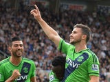 Shane Long of Southampton (7) celebrates with Victor Wanyama (12) and Graziano Pelle (L) as he scores their second goal during the Barclays Premier League match between Newcastle United and Southampton at St James' Park on August 9, 2015