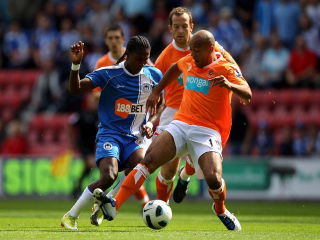 Hugo Rodallega of Wigan Athletic is challenged by Alex Baptiste of Blackpool during the Barclays Premier League match between Wigan Athletic and Blackpool at the DW Stadium on August 14, 2010