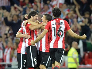 Athletic Bilbao's defender Mikel San Jose is congratulated by teammates midfielder Benat Etxebarria (L), midfielder Oscar de Marcos (3rd L) and defender Xabier Etxeita (R) after scoring during the Spanish Supercup first-leg football match Athletic Club Bi