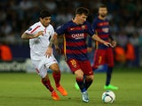 Lionel Messi of Barcelona holds off a challenge from Ever Banega of Sevilla during the UEFA Super Cup between Barcelona and Sevilla FC at Dinamo Arena on August 11, 2015