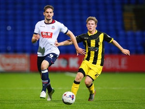 Dorian Dervite of Bolton Wanderers and Matt Palmer of Burton Albion watch the ball during the Capital One Cup first round match between Bolton Wanderers and Burton Albion at Macron Stadium on August 11, 2015