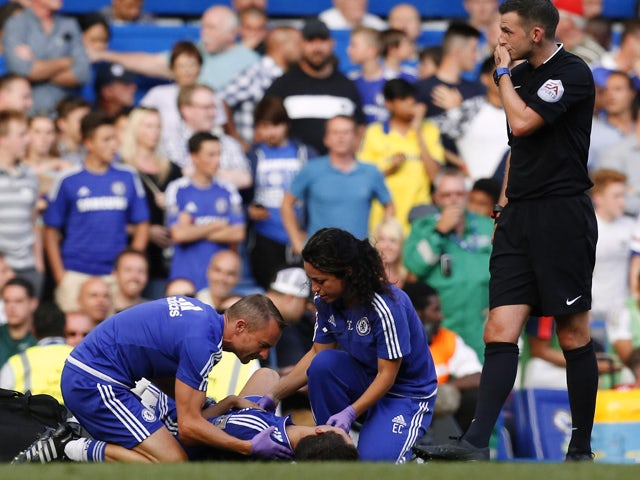 Chelsea doctor Eva Carneiro and head physio Jon Fearn treat Chelsea's Belgian midfielder Eden Hazard late on next to referee Michael Oliver during the English Premier League football match between Chelsea and Swansea City at Stamford Bridge in London on A