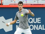Novak Djokovic of Serbia hits a return against Jack Sock of the USA during day four of the Rogers Cup at Uniprix Stadium on August 13, 2015