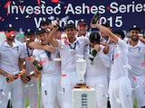 England's captain Alastair Cook holds up the replica Ashes urn as England players celebrate their series victory after the fourth day of the fifth Ashes cricket test match between England and Australia at The Oval cricket ground in London, on August 23, 2