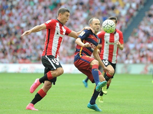 Andres Iniesta of FC Barcelona is tackled by Oscar de Marcos of Athletic Club during the La Liga match between Athletic Club and FC Barcelona at San Mames Stadium on August 23, 2015