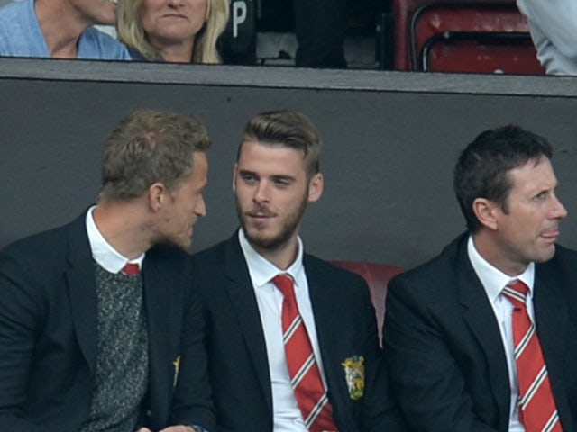 Manchester United's Spanish goalkeeper David de Gea (centre right) sits in the stands ahead of the English Premier League football match between Manchester United and Newcastle United at Old Trafford in Manchester, north west England, on August 22, 2015