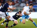 Italy's Giovanbattista Venditti tries to avoid a tackle during the Rugby World Cup Test match Italy Vs Scotland on August 22, 2015