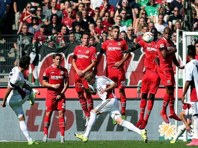 Leverkusen's midfielder Hakan Calhanoglu (L) scores his team's opening goal during the German first division Bundesliga football match Hannover 96 v Bayer 04 Leverkusen, on August 22, 2015