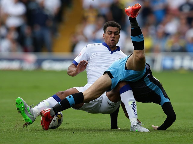 Liam Palmer of Sheffield Wednesday FC falls over Stuart Dallas of Leeds United FC in a tackle during the Sky Bet Championship match between Leeds United and Sheffield Wednesday at Elland Road on August 22, 2015