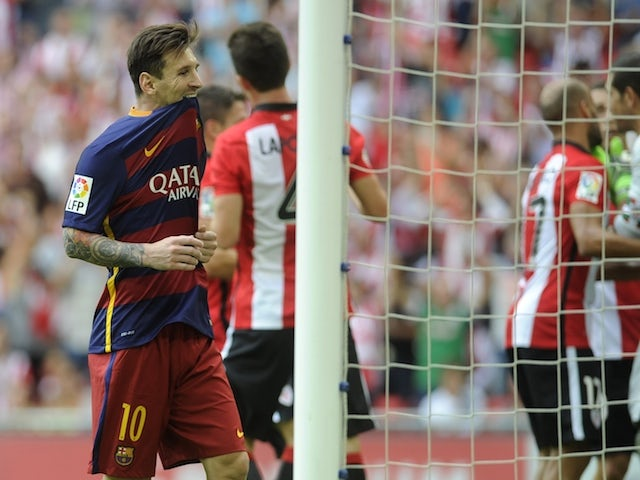 Barcelona's Argentinian forward Lionel Messi (L) bites his shirt after missing a penalty during the Spanish league football match Athletic Club Bilbao vs FC Barcelona at the San Mames stadium in Bilbao on August 23, 2015