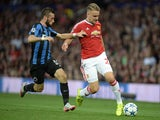 Club Brugge's Belgian forward Tuur Dierckx (L) challenges Manchester United's English defender Luke Shaw during the UEFA Champions League play off football match between Manchester United and Club Brugge at Old Trafford in Manchester, north west England,