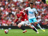 Wayne Rooney of Manchester United and Aleksandar Mitrovic of Newcastle United compete for the ball during the Barclays Premier League match between Manchester United and Newcastle United at Old Trafford on August 22, 2015