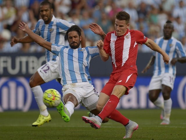 Malaga's Argentinian defender Marcos Alberto Angeleri (L) vies with Sevilla's French forward Kevin Gameiro during the Spanish league football match Malaga CF vs Sevilla FC at La Rosaleda stadium in Malaga on August 21, 2015