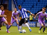 Lewis McGugan of Sheffield is challenged by Orlando Sa and Stephen Quinn of Reading during the Sky Bet Championship match between Sheffield Wednesday and Reading at Hillsborough Stadium on August 19, 2015