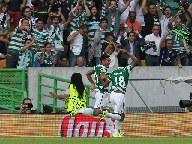 Sporting's forward Teofilo Gutierrez celebrates scoring a goal with Sporting's forward Andre Carrillo during the UEFA Champions League qualifying round play-off first leg match between Sporting CP and CSKA Moscow at Estadio Jose Alvalade on August 18, 201