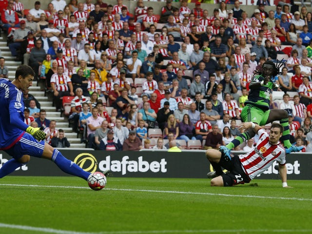 Swansea City's French striker Bafetimbi Gomis (top right) scores the opening goal against Sunderland during the English Premier League football match between Sunderland and Swansea City at the Stadium of Light in Sunderland, north east England on August 2