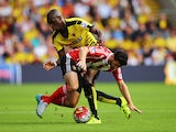 Shane Long of Southampton is challenged by Allan-Romeo Nyom of Watford during the Barclays Premier League match between Watford and Southampton at Vicarage Road on August 23, 2015
