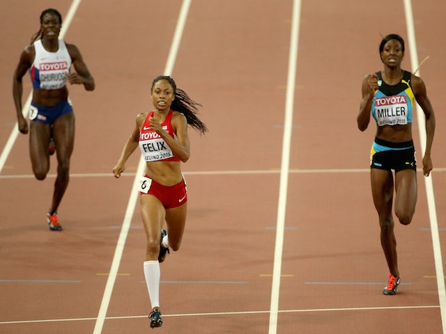 Allyson Felix of the United States (C) crosses the finish line to win gold ahead of Shaunae Miller of the Bahamas (R)in the Women's 400 metres Final during day six of the 15th IAAF World Athletics Championships Beijing 2015 at Beijing National Stadium on