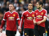 Daley Blind (R) of Manchester United looks dejected with Wayne Rooney (L) and Memphis Depay after Barclays Premier League match between Swansea City and Manchester United at Liberty Stadium on August 30, 2015