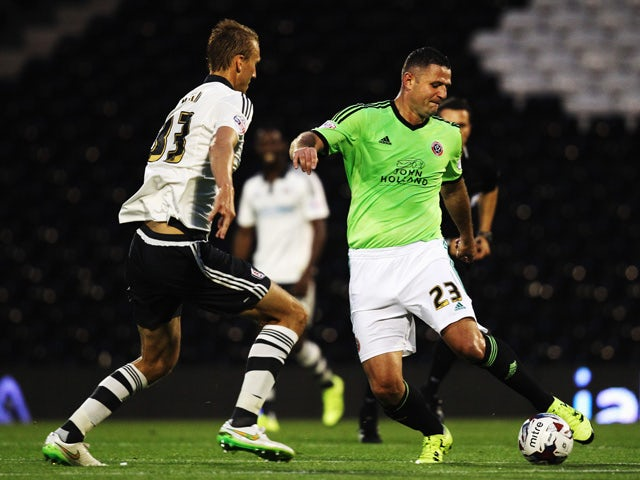 Dan Burn of Fulham and Michael Higdon of Sheffield United challenge for the ball during the Capital One League Cup Second Round match between Fulham and Sheffield United at Craven Cottage on August 25, 2015